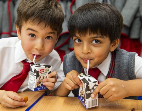 two young boys drinking from milk cartons