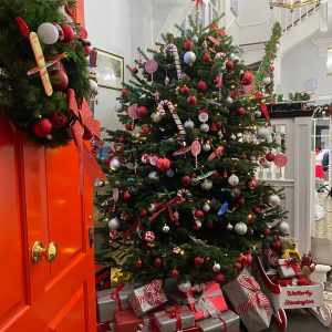 Image of the red door with a wreath, and a Christmas tree with several red and silver parcels underneath