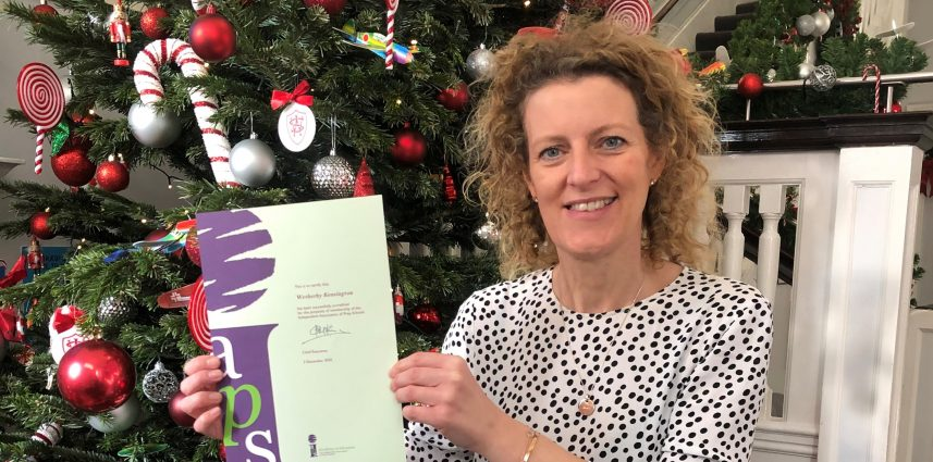 teacher holding up certificate in front of a christmas tree