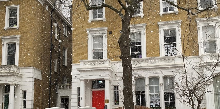 A shot of a house with cars parked outside, and it is snowing.