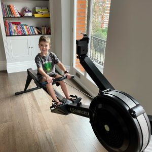 A young boy in their living room at home sat on a rowing machine.
