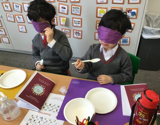 Two kids sat at a desk with plastic spoons, wearing purple blindfolds